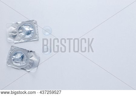 Two Contact Lenses In A Closed Package And Two Open Contact Lenses Lie On The Side On A White Backgr