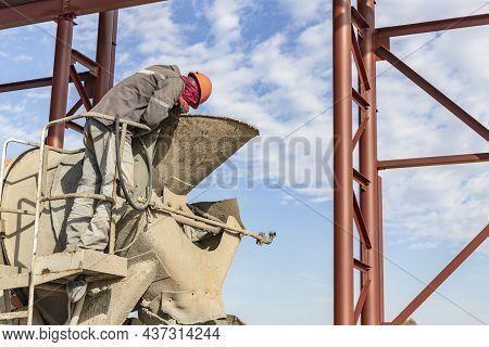 A Worker On A Concrete Mixer Truck Prepares To Concrete A Reinforced Concrete Structure. Equipment F