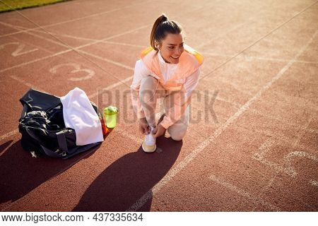 caucasian young adult female kneeling on one knee at the athletic track, tying shoelaces, smiling, looking  away with her headphones in her ears