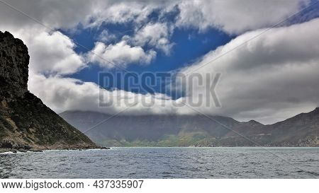 Coastal Cliffs Of The Atlantic Ocean Bay Against The Blue Sky. There Are White Cumulus Clouds Above