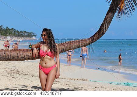 Punta Cana, Dominican Republic - October 2021: Smiling Woman In Sunglasses And Pink Bikini Posing Ne