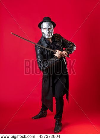 A Mysterious Ninja Assassin In A Noir Style. A Man In Black Clothes With A Cape And Hat, Covers His