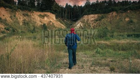 Hiker Walks With A Backpack In A Large, Sandy Quarry At Sunset. The Quarry Is Overgrown With Grass A