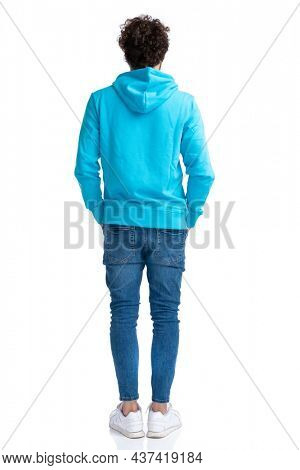 back view of curly casual man in blue hoodie holding hands in pockets and waiting in line while posing against white background in studio