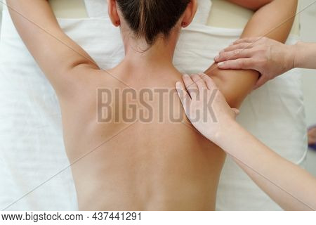 Above shot of back of young woman visiting spa salon where masseur doing her body massage