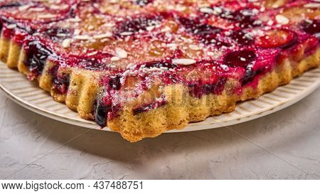 Macro Panoramic Orientation Pie Or Tart With Plums On Plate On Light Wooden Background. Selective Fo