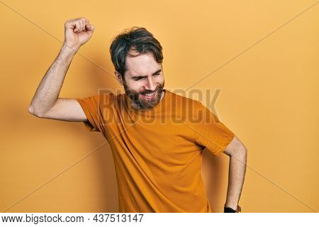 Caucasian man with beard wearing casual yellow t shirt dancing happy and cheerful, smiling moving casual and confident listening to music