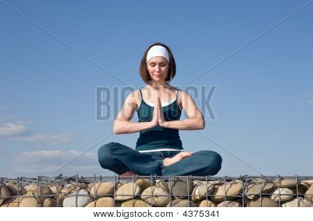 Woman Making Yoga Exercises In Top Of A Stone Wall