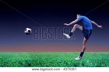 a young soccer player shots a ball in a grass field ** Note: Slight blurriness, best at smaller sizes poster