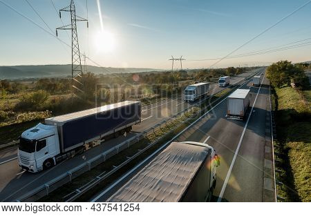 Convoys Or Caravans Of Transportation Trucks Passing On A Highway At Sunset. Highway Transit Transpo