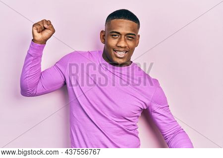 Young black man wearing casual pink sweater dancing happy and cheerful, smiling moving casual and confident listening to music