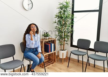 Young latin woman talking on the smartphone sitting on chair at waiting room