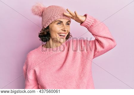 Young brunette woman wearing cute wool cap very happy and smiling looking far away with hand over head. searching concept.