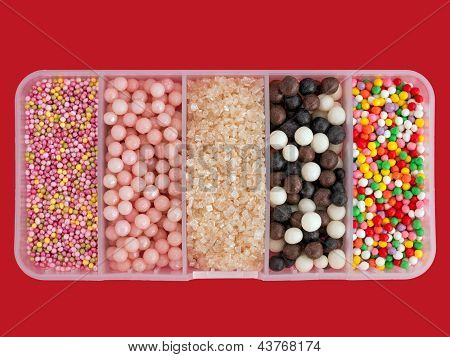 Assorted Cake Sugar Decorations - Sprinkles Isolated Over Red