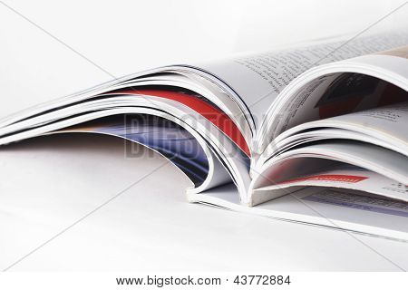 stack of magazines, with reflection, on white background