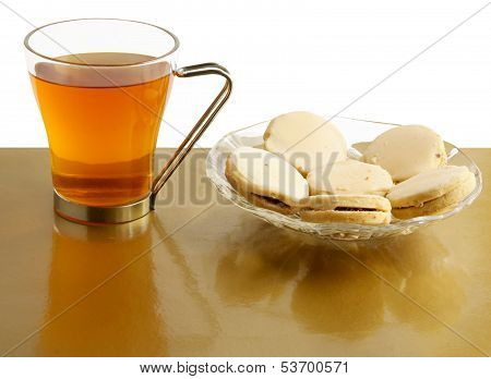 glass of hot tea and tasty iced cakes