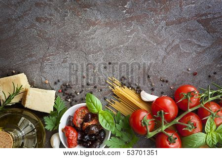 Italian food background, with vine tomatoes, basil, spaghetti, mushrooms, olives, parmesan, olive oil, garlic, peppercorns, rosemary, parsley and thyme.  Slate background.