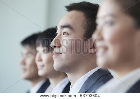 Four business people sitting in row