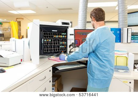 Rear view of male lab tech performing hematology analysis in hospital lab