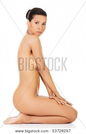Attractive naked woman sitting on knees. Side view. isolated on white.