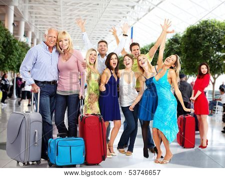 Group of happy people in airport. Holiday travel background.