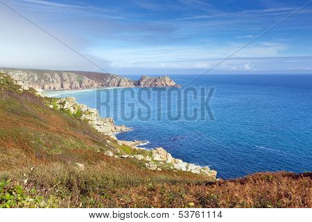 Coast of Cornwall England in autumn with mist and blue sky near the Minack Theatre and Porthcurno