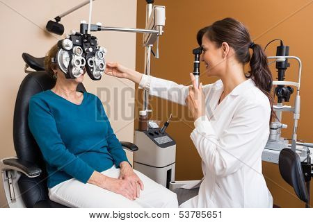 Young female optometrist examining senior woman's eyes in store
