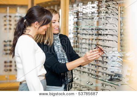 Happy woman with salesgirl examining eyeglasses in optician store