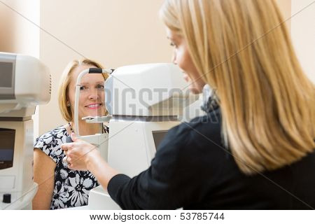 Young Optometrist measuring patients eye pressure with tonometer poster