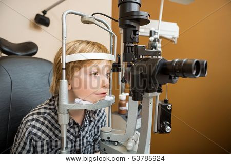 Preadolescent boy undergoing eye examination with slit lamp in store