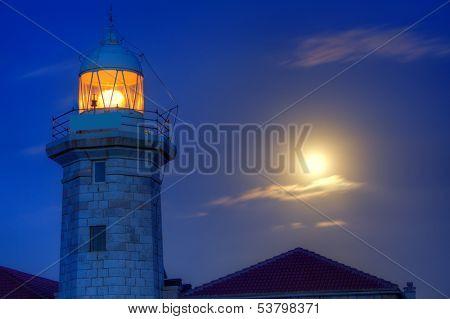 Ciutadella Menorca Punta Nati lighthouse with moon shining in sky poster