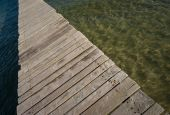 Wooden pier made of planks and dividing methaforically water in dark and bright part poster