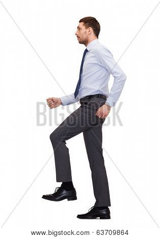 business and education concept - serious businessman stepping on imaginary step