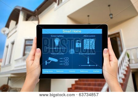 Female hands hold a tablet computer with system of smart house on a screen