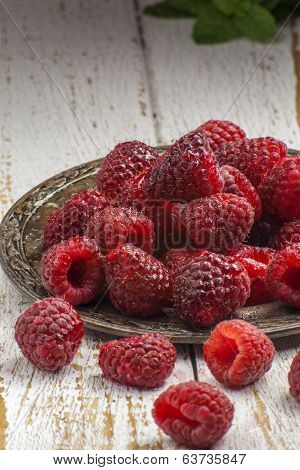 freshly picked raspberries on a picnic table