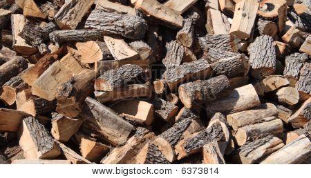background of randomly piled split firewood logs poster