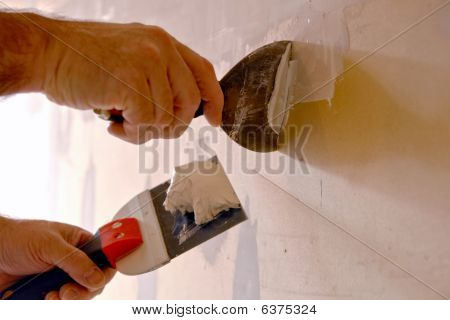 Construction Worker Spackling Wall With Joint Compound