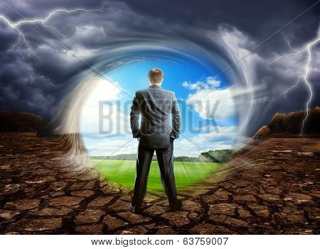 Businessman staying against cloudy blue sky