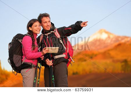 Tablet PC - hiking couple using travel app or map on hike. Man and woman hikers looking at view pointing and showing during hike on volcano Teide, Tenerife, Canary Islands, Spain.