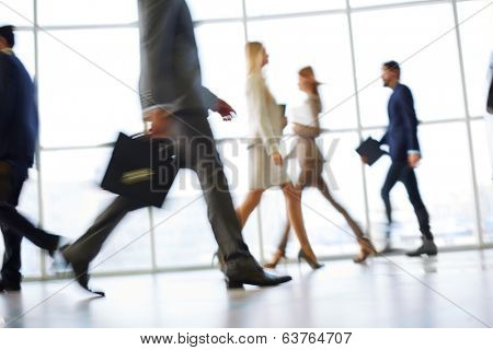 White collar workers going down office corridor during working day