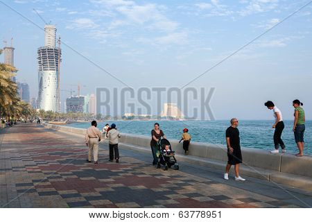 DOHA, QATAR - NOVEMBER 18, 2007: Expats and local citizens enjoy exercise on the Corniche, while building work goes on at a frantic rate to create the towers of the city's skyline.