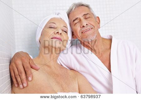 Happy senior couple sitting in relaxation room after sauna session in spa