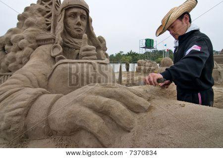 Sand sculpture artist working on his sculpture