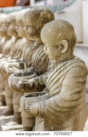 Row Of Stucco Monks In Temple.