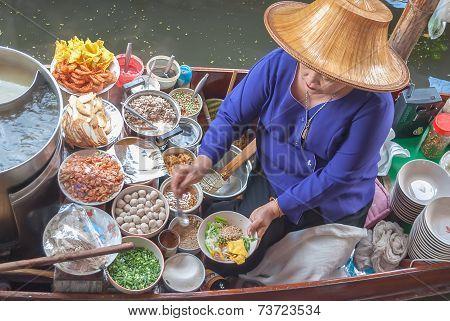 A Woman Makes Nooddle Thai Food At Damnoen Saduak Floating Market