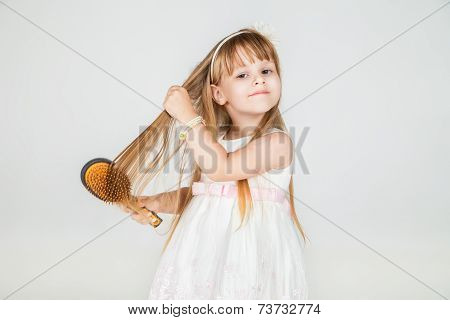 Smiling little girl brushing her hair closeup