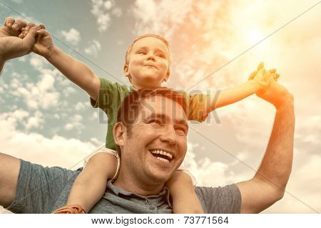 Son seating on the father under beautiful sky