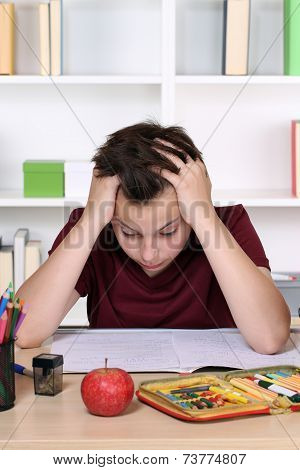 Young Student Desperate And Overworked With Homework At School