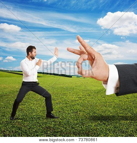 concept photo of conflict between subordinate and boss. angry young businessman ready for fight with big flick of his boss. photo at outdoor