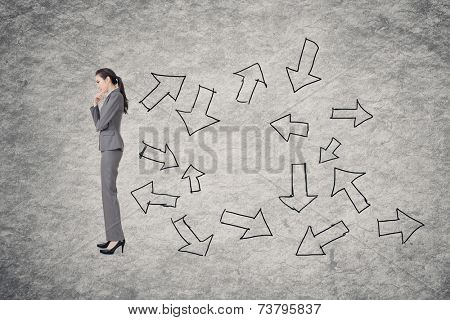 Confused concept with Asian business woman thinking with hand drawing graphic behind her.